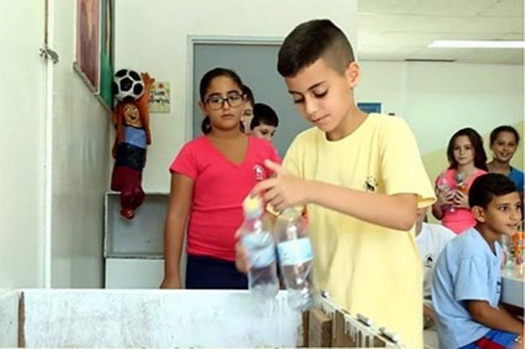 תלמידים אוספים בקבוקים למחזור